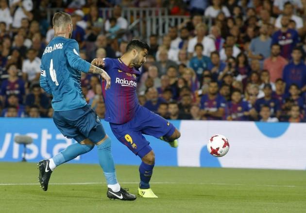 Luis Suárez dispara a puerta ante la presencia de Sergio Ramos.