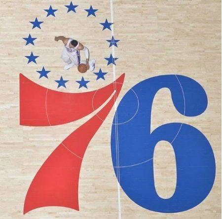Ben Simmons jugando sobre el logo de los Philadelphia 76ers.